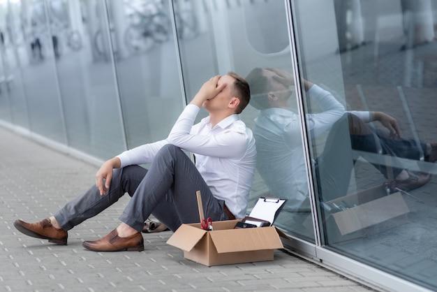 Ein junger entlassener büroangestellter sitzt unter seinem büro. neben ihm ist sein briefpapier. der mann ist gestresst.