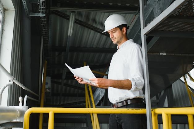 Ein junger erfolgreicher ingenieur mit einer zeichnung in der hand steht auf dem gebiet einer modernen fabrik