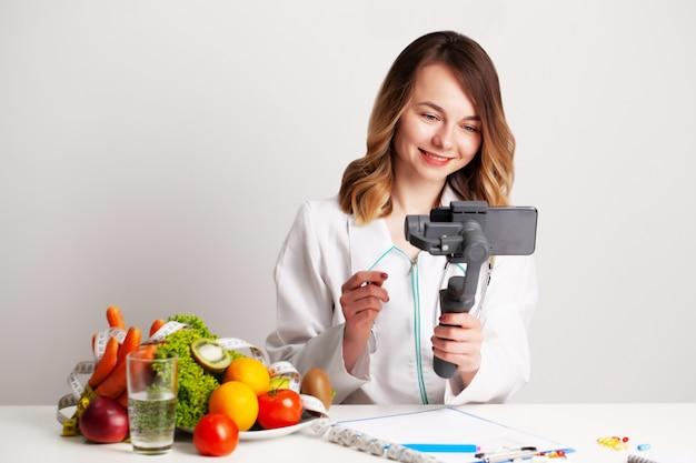 Ein junger ernährungsberater in einem sprechzimmer schreibt einen blog über gewichtsverlust und gesunde ernährung
