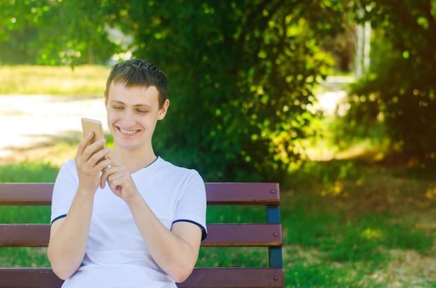 Ein junger europäer sitzt auf einer bank in einem stadtpark und zeigt mit dem finger auf das telefon.