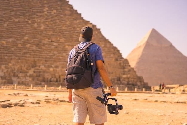 Ein junger fotograf an der pyramide von cheops die größte pyramide. die pyramiden von gizeh sind das älteste grabdenkmal der welt. in der stadt kairo, ägypten