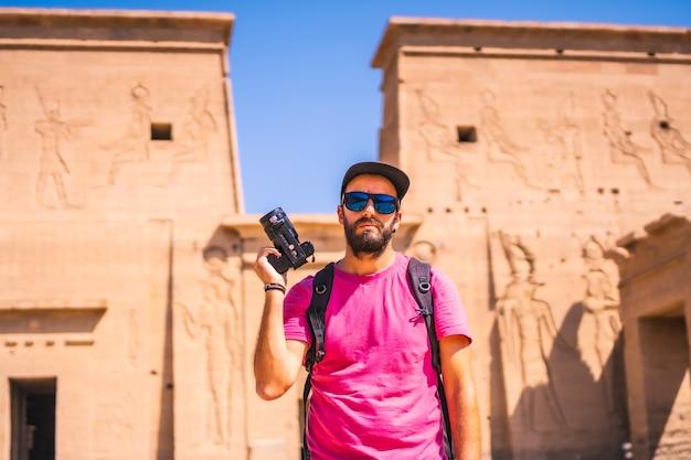 Ein junger fotograf im tempel von philae, einem griechisch-römischen bau, einem tempel, der isis, der göttin der liebe, gewidmet ist. assuan. ägyptisch