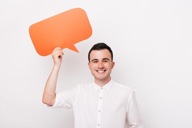 Ein junger fröhlicher mann lächelt und hält eine blasenrede auf einem weißen hintergrund.