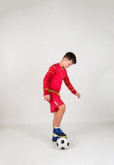 Ein junger fußballspieler in roter uniform spielt mit einem fußball auf weißem hintergrund mit platz für text