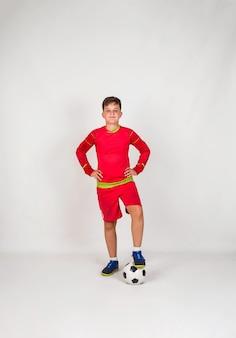 Ein junger fußballspieler in roter uniform steht mit einem fußball auf weißem hintergrund mit platz für text
