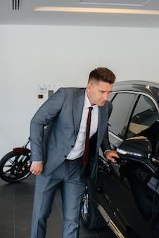 Ein junger geschäftsmann betrachtet ein neues auto in einem autohaus. ein auto kaufen.