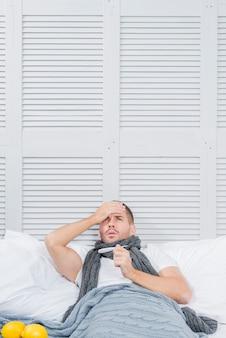 Ein junger geschäftsmann, der auf dem bett überprüft die stirntemperatur mit seiner hand liegt