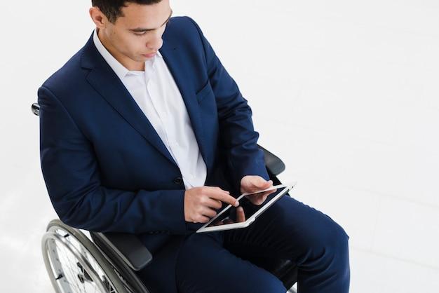 Ein junger geschäftsmann, der auf rollstuhl unter verwendung der digitalen tablette gegen weißen hintergrund sitzt