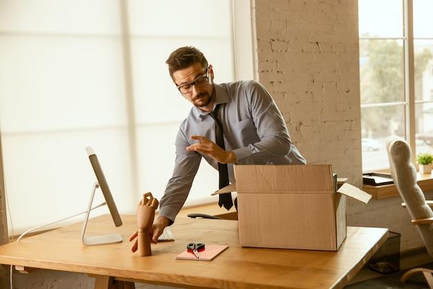Ein junger geschäftsmann, der im büro umzieht und einen neuen arbeitsplatz bekommt. junger kaukasischer männlicher büroangestellter rüstet neues kabinett nach beförderung aus. sieht glücklich aus