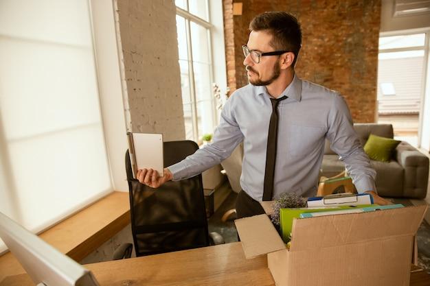 Ein junger geschäftsmann, der im büro umzieht und einen neuen arbeitsplatz bekommt. junger kaukasischer männlicher büroangestellter rüstet neues kabinett nach beförderung aus
