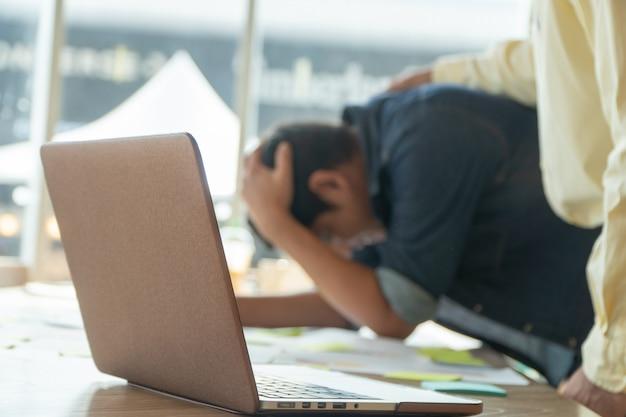 Ein junger geschäftsmann hält seinen kopf in den kopf wegen der enttäuschung.