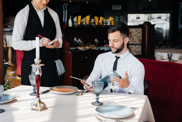 Ein junger geschäftsmann in einem feinen restaurant begutachtet die speisekarte und bestellt einem jungen kellner in stilvoller schürze. kundendienst.