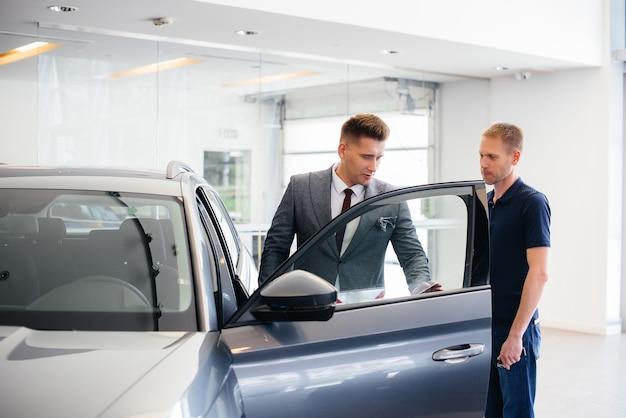 Ein junger geschäftsmann mit einem verkäufer schaut sich ein neues auto in einem autohaus an. ein auto kaufen.
