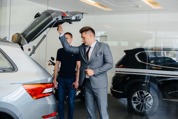 Ein junger geschäftsmann mit einem verkäufer untersucht den kofferraum eines neuwagens in einem autohaus. ein auto kaufen.