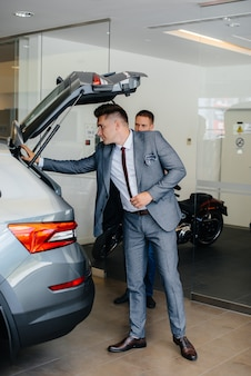 Ein junger geschäftsmann mit einem verkäufer untersucht den kofferraum eines neuwagens in einem autohaus