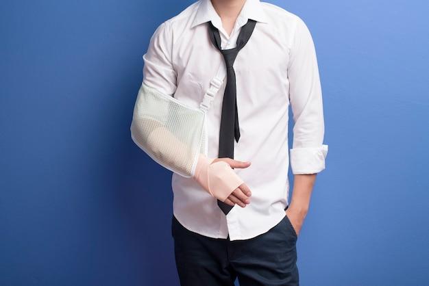 Ein junger geschäftsmann mit einem verletzten arm in einer schlinge über blauer wand, versicherungs- und gesundheitskonzept
