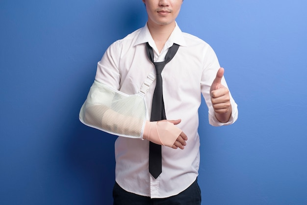 Ein junger geschäftsmann mit einem verletzten arm in einer schlinge über der blauen wand