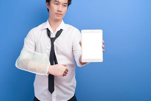 Ein junger geschäftsmann mit einem verletzten arm in einer schlinge unter verwendung einer tablette über blauem hintergrund im studio-, versicherungs- und gesundheitskonzept