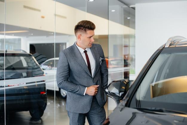 Ein junger geschäftsmann schaut sich ein neues auto in einem autohaus an