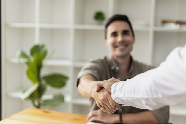 Ein junger geschäftsmann schüttelt nach einer diskussion einem geschäftspartner die hand. zwei geschäftsleute, die hände rütteln. ein händedruck ist eine geste des respekts oder der gratulation. business-etikette-konzept.