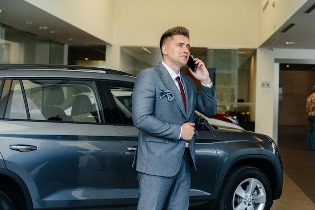 Ein junger geschäftsmann telefoniert nach dem kauf eines neuen autos