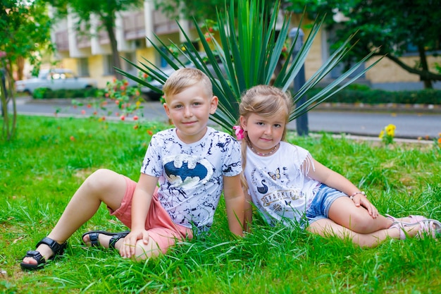 Ein junger glücklicher junge und seine kleine nette schwester, die an einem warmen sommertag gehen.