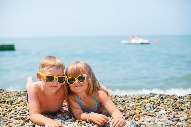 Ein junger glücklicher junge und seine kleine nette schwester, die auf das seeufer an einem warmen sommertag gehen.