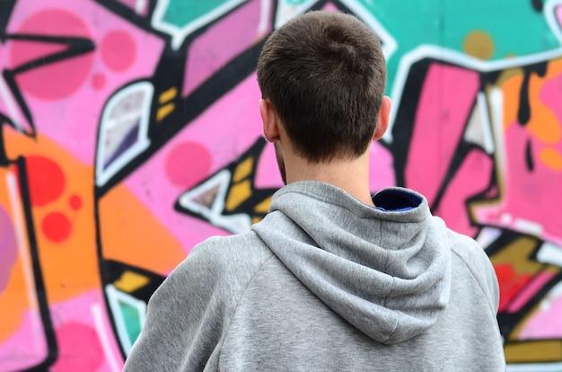 Ein junger graffitikünstler in einem grauen hoodie betrachtet die wand mit