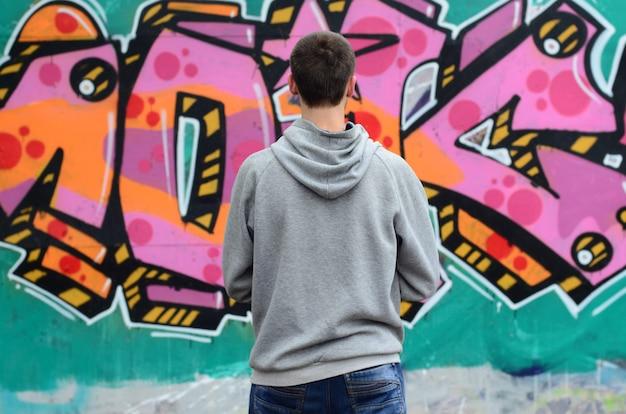 Ein junger graffitikünstler in einem grauen hoodie betrachtet die wand