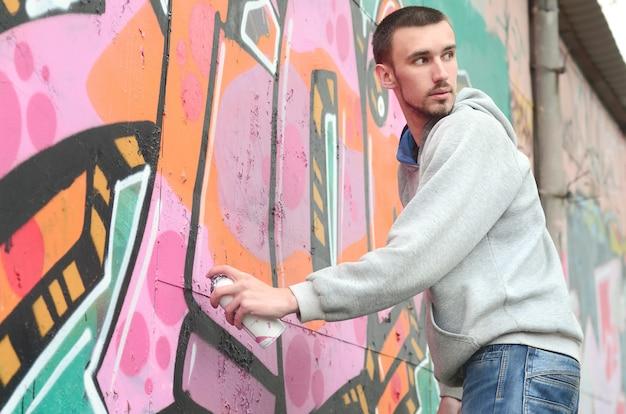 Ein junger graffitikünstler schaut sich beim zeichnen um. vandal versucht es