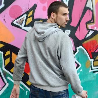 Ein junger graffitikünstler schaut sich beim zeichnen um.