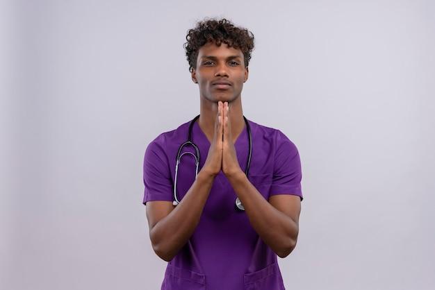Ein junger gut aussehender dunkelhäutiger männlicher arzt mit lockigem haar in violetter uniform mit stethoskop, das die hand zusammenhält