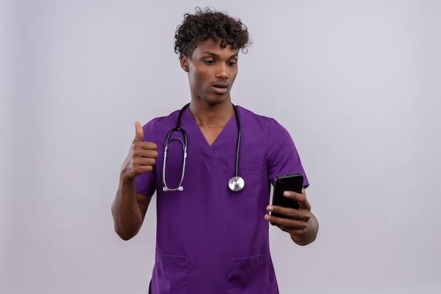 Ein junger gut aussehender dunkelhäutiger männlicher arzt mit lockigem haar in violetter uniform mit stethoskop, der auf sein smartphone schaut, während er eine gute geste zeigt