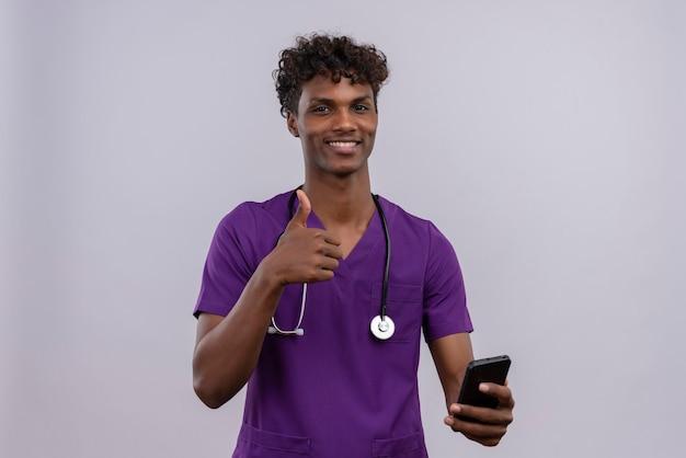 Ein junger gut aussehender dunkelhäutiger männlicher arzt mit lockigem haar in violetter uniform mit stethoskop hält sein smartphone und zeigt eine gute geste