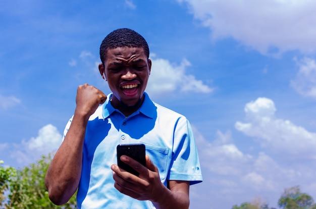 Ein junger, gutaussehender afrikanischer junge war schockiert über das, was er auf seinem handy sah