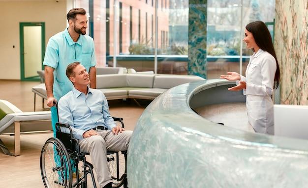 Ein junger gutaussehender arzt mit seiner älteren behinderten person im rollstuhl näherte sich der rezeption der klinik.