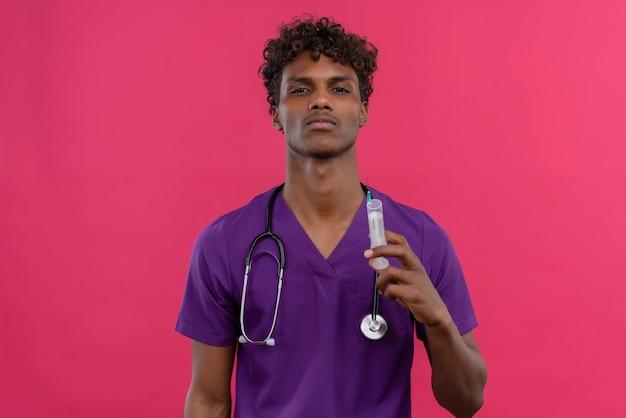 Ein junger gutaussehender dunkelhäutiger arzt mit lockigem haar, der eine violette uniform mit einer injektionsspritze trägt