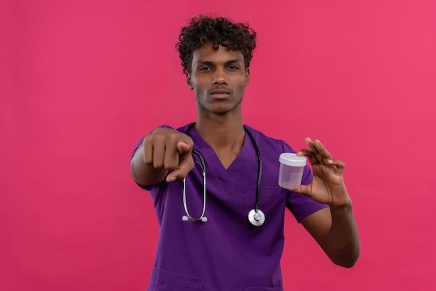 Ein junger gutaussehender dunkelhäutiger arzt mit lockigem haar in violetter uniform mit stethoskop, das auf eine kamera zeigt, die ein plastikprobenglas hält