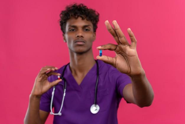Ein junger gutaussehender dunkelhäutiger arzt mit lockigem haar in violetter uniform mit stethoskop, das pillen betrachtet