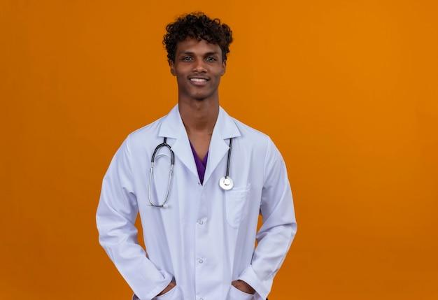 Ein junger gutaussehender dunkelhäutiger mann mit lockigem haar, der einen weißen kittel mit stethoskop trägt und hände auf taschen legt
