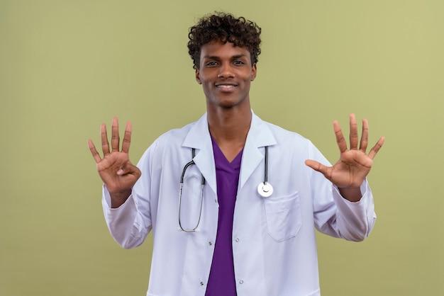 Ein junger gutaussehender dunkelhäutiger mann mit lockigem haar, der einen weißen kittel mit stethoskop trägt und nummer neun auf einer grünfläche zeigt