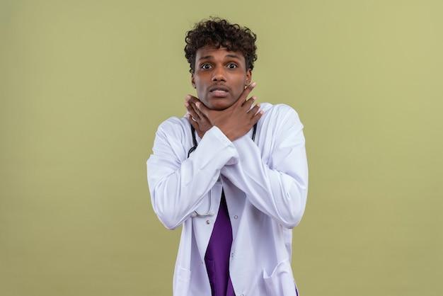 Ein junger gutaussehender dunkelhäutiger mann mit lockigem haar, der einen weißen kittel mit stethoskop trägt und sich auf einer grünfläche gestresst fühlt