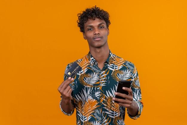 Ein junger gutaussehender dunkelhäutiger mann mit lockigem haar im bedruckten hemd der blätter, das kreditkarte zeigt, während handy hält
