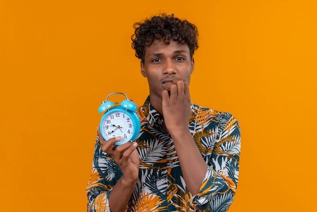 Ein junger gutaussehender dunkelhäutiger mann mit lockigem haar im blatt bedruckten hemd, das blauen wecker mit hand am kinn hält