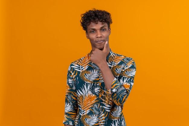Ein junger gutaussehender dunkelhäutiger mann mit lockigem haar im blatt bedruckten hemd, das hand am kinn hält