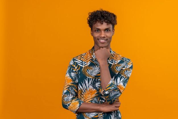 Ein junger gutaussehender dunkelhäutiger mann mit lockigem haar im blattbedruckten hemd lächelt, während er seine faust am kinn hält