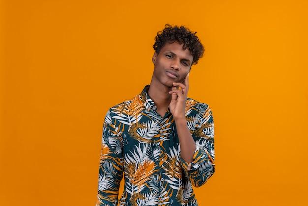 Ein junger gutaussehender dunkelhäutiger mann mit lockigem haar in blättern bedrucktes hemd, das denkt und hand auf wange hält
