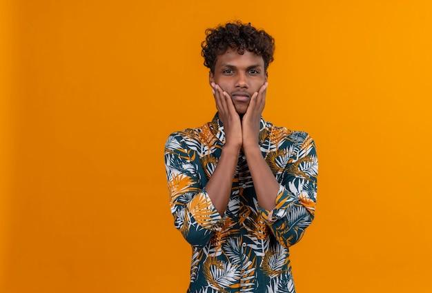 Ein junger gutaussehender dunkelhäutiger mann mit lockigem haar in blättern bedrucktes hemd, das hände auf wange mit verwirrtem gesicht hält