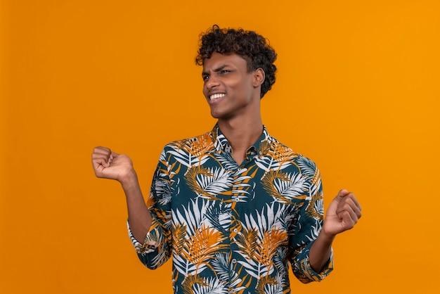 Ein junger gutaussehender dunkelhäutiger mann mit lockigem haar in blättern bedrucktes hemd mit unzufriedenem gesicht