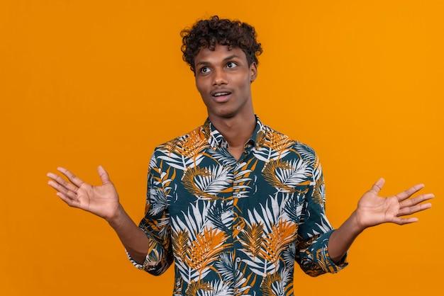 Ein junger gutaussehender dunkelhäutiger mann mit lockigem haar in einem bedruckten hemd mit überraschtem gesichtsausdruck
